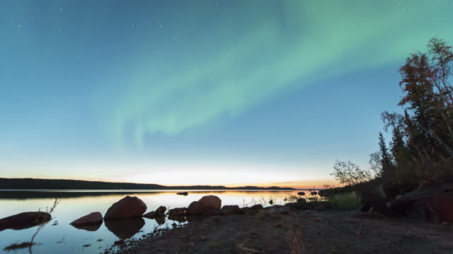 WS T/L View of aurora during early summer with sun still setting over calm lake with reflection / Yellowknife, Northwest Territories, Canada