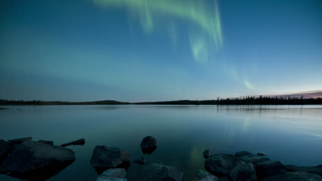 ws t/l view of aurora with rocks in foreground during early summer with slow dolly movement / yellowknife, northwest territories, canada  - polarlicht stock-videos und b-roll-filmmaterial