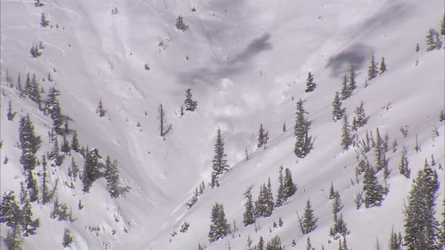 WS PAN TD View of avalanche exploding through snowy ridge / Bozeman, Montana, USA