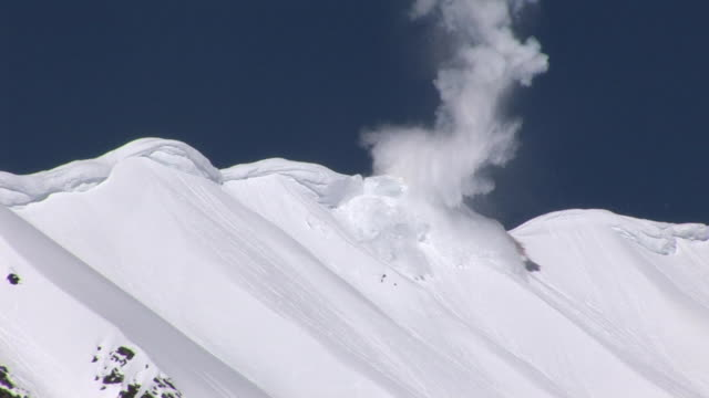 WS View of avalanche exploding through snowy ridge / Revelstoke, British Columbia, Canada