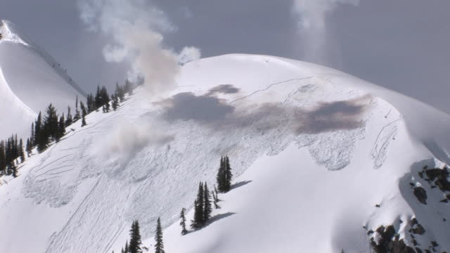 WS ZI ZO TD View of avalanche exploding through snowy ridge / Revelstoke, British Columbia, Canada