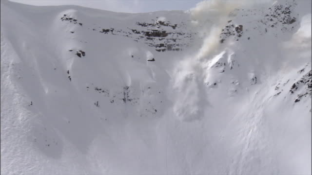 MS TD View of Avalanche rolling down steep mountain side / Revelstoke, British Columbia, Canada