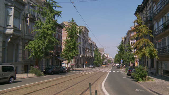 ws view of avenue brugmann with traffic moving on street / brussels, brussels capital region, belgium - ベルギー点の映像素材/bロール