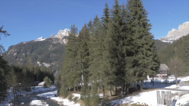 view of avisio river in canazei on sunny day in winter, province of trento, italian dolomites, italy, europe - canazei video stock e b–roll