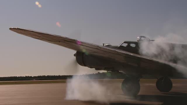 stockvideo's en b-roll-footage met ms view of b-17 engine start in silhouette / boston, massachusettes, united states - start  en landingsbaan