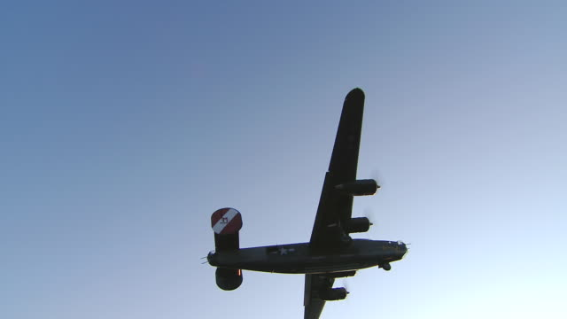 aerial ws view of b-24 bomber falls out of frame, silhouette on blue sky / boston, massachusettes, united states - bomber plane stock videos and b-roll footage