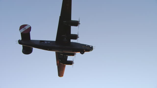 aerial ws view of b-24 bomber silhouette on blue sky / boston, massachusettes, united states - bomber plane stock videos and b-roll footage
