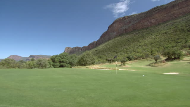 vidéos et rushes de ws view of ball falling onto putting green, legend golf and safari resort, waterberg / limpopo, south africa - balle de golf