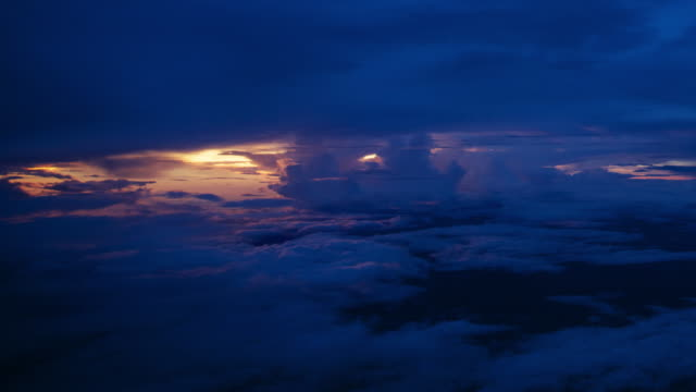 ws aerial t/l view of bank of cumulus clouds in early morning pink light as deep blue clouds / hanoi, in flight - ターコイズブルー点の映像素材/bロール