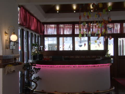 view of bar area in a restaurant lit with pink lights and an old fashioned brass globe sconce on the wall. - messing about stock-videos und b-roll-filmmaterial