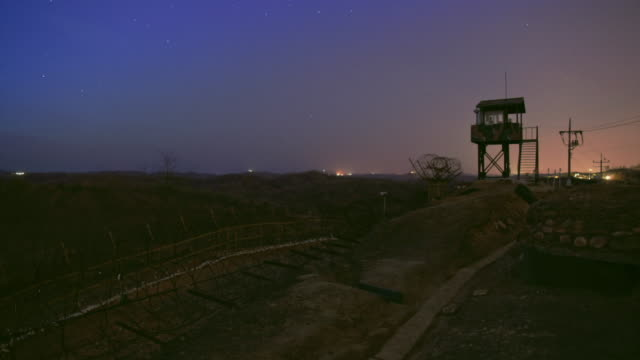 View of barbed-wire fence and guard post at night in DMZ (Demilitarized zone, A strip of land running across the Korean Peninsula), South korea