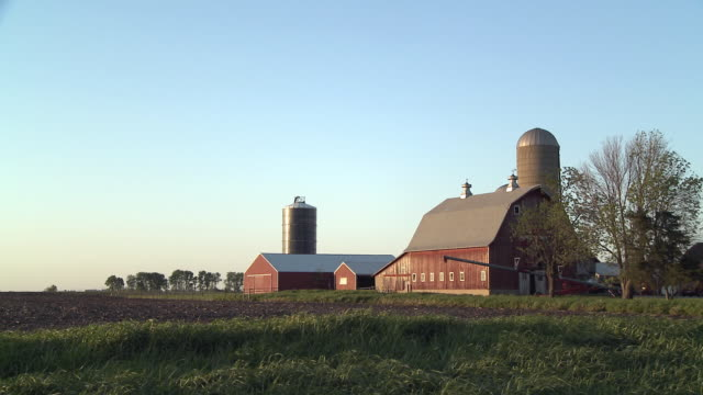 ws view of barn and silo in field / newark, illinois, usa - barn stock videos and b-roll footage