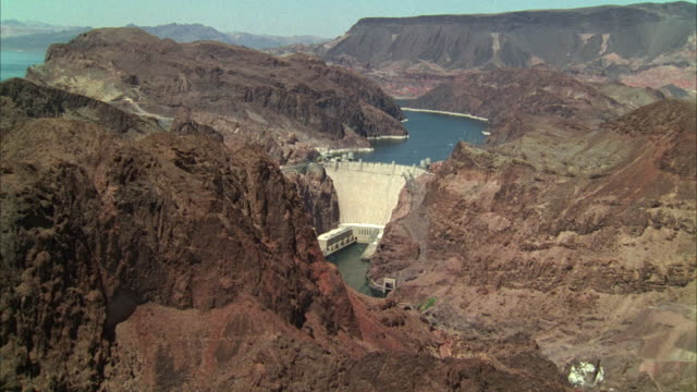 vídeos de stock, filmes e b-roll de ws pov aerial view of barren rugged rock mountains to hoover dam with lake mead in background / nevada, arizona, usa - represa hoover