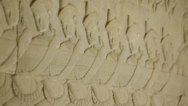 CU POV View of bas relief carvings of Sea Churning of Milk engraving on wall of Angkor Wat Temple / Siem Reap, Siem Reap Province, Cambodia