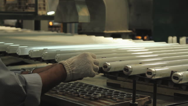 CU ZI View of base mounting process of fluorescent lamps, Surya Roshni Limited / Malanpur, Madhya Pradesh, India