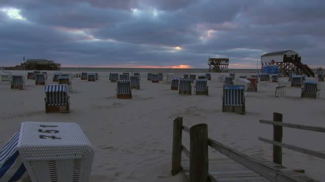 ws view of beach and relax chairs during sunset, north sea north frisia, / st. peter ording, schleswig holstein, germany - north frisian islands stock videos & royalty-free footage