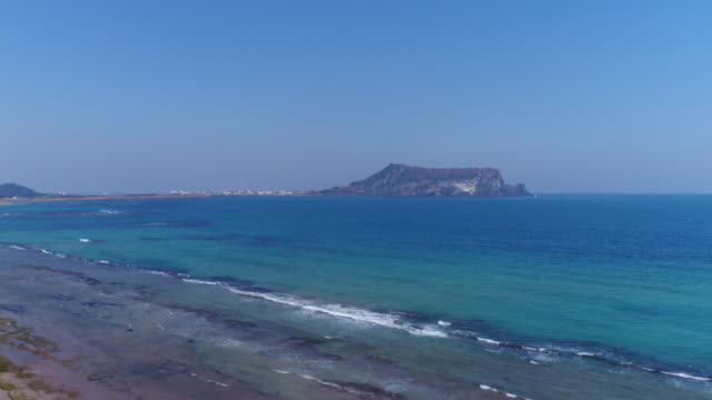 View of beach and Seongsanilchulbong Tuff Cone (Korea Natural Monument 420) in distance