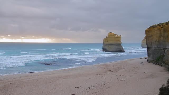 vídeos de stock, filmes e b-roll de ws pan view of beach and spectacular towering cliffs of twelve apostles / port campbell, victoria, australia / port campbell, victoria, australia - coluna de calcário marítimo