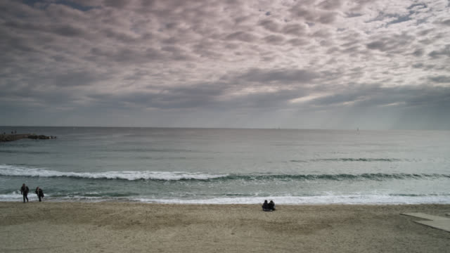 ws pan view of beach at sunset without very few people / barcelona, catalunya, spain - altocumulus stock videos and b-roll footage