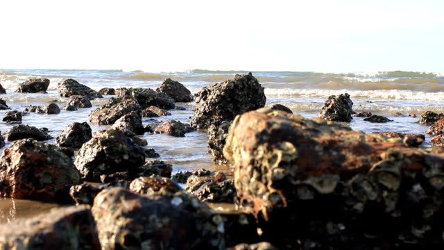 view of beach peaceful of rocky shoreline in thailand. - bugtiger stock videos and b-roll footage