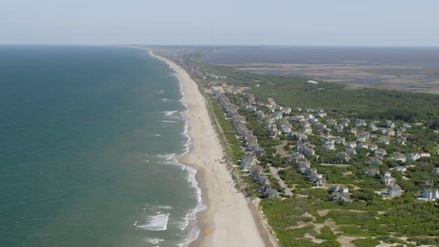 ws aerial pov view of beach with townscape / corolla, north carolina, united states - north carolina beach stock videos & royalty-free footage