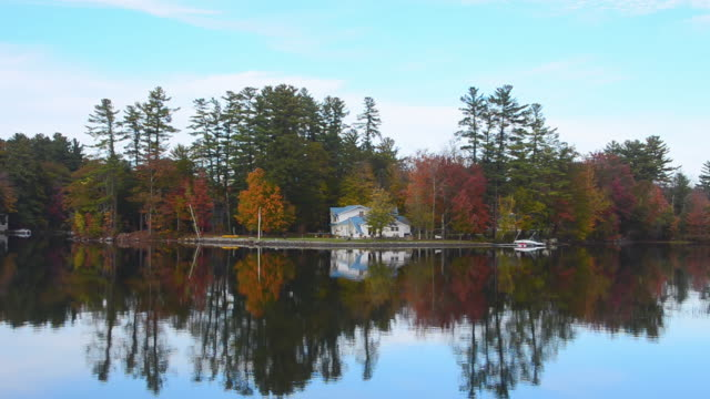 ws view of beautiful fall scene of lake pennasseewassee with summer homes and fall colors in leaf peeping october with reflections in water in northern new england / norway, maine, united states - symmetry stock videos & royalty-free footage