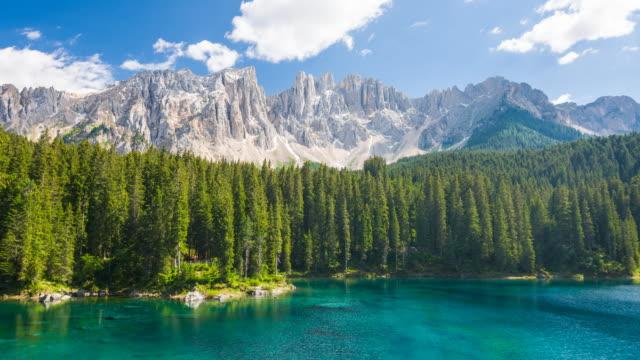 松の木、晴れた日の背景の山に囲まれた美しいターコイズ ブルー色の湖のビュー - mountain range点の映像素材/bロール