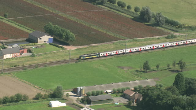 MS AERIAL ZI TS View of Belgian Train passing through farm land / Flanders, Belgium