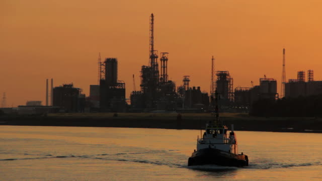 WS View of Belgium, Port of Antwerp, tow boat against skyline of petroleum industry at dusk /Antwerp, Antwerp, Belgium