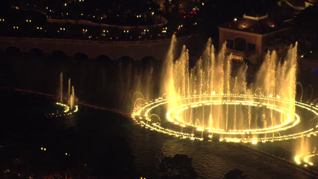 ms aerial view of bellagio water fountains performance at night with lights on / las vegas, nevada, united states - fountain stock videos & royalty-free footage