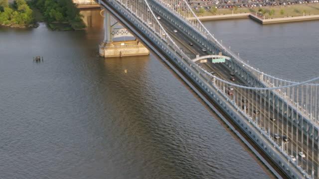 ms aerial view of benjamin franklin bridge with passing cars and baseball  ground at end / philadelphia - ベンフランクリン橋点の映像素材/bロール