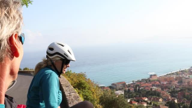 vídeos de stock, filmes e b-roll de vista do pov de casal ciclista acima do mar, vila - casal de meia idade
