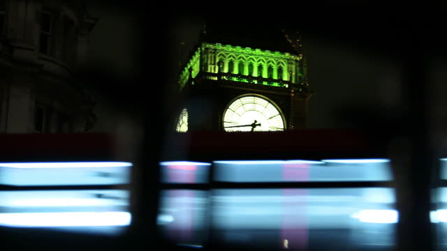 view of big ben at night through railings, london, united kingdom - big ben stock-videos und b-roll-filmmaterial
