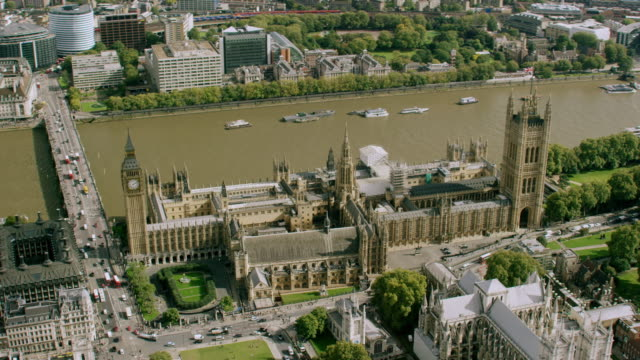 ws aerial pov view of big ben building and london eye with thames river in city / london, england, united kingdom - ビッグベン点の映像素材/bロール