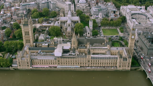 ws aerial pov view of big ben building with thames river in city / london, england, united kingdom - parliament building stock videos & royalty-free footage