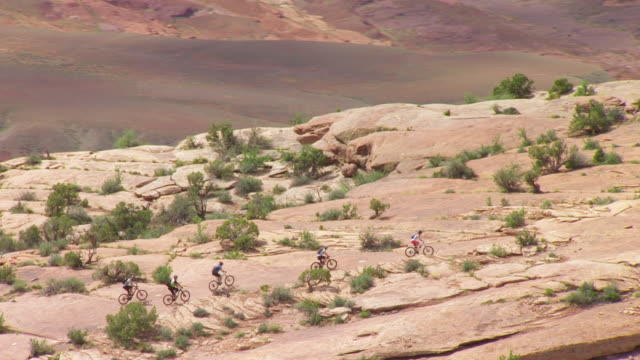 ws aerial ds zo view of bikers and cliffs / moab, utah, united states - moab utah stock-videos und b-roll-filmmaterial