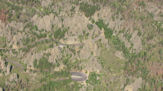 ws aerial view of birds eye view over cathedral spires with cars driving around them in custer state park / south dakota, united states - custer staatspark stock-videos und b-roll-filmmaterial