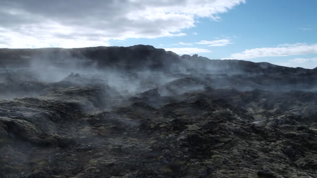 ws view of black volcanic rock, steam coming out from ground and blowing across landscape at leirhnjukur / krafla, myvatn region, iceland - solid stock videos & royalty-free footage