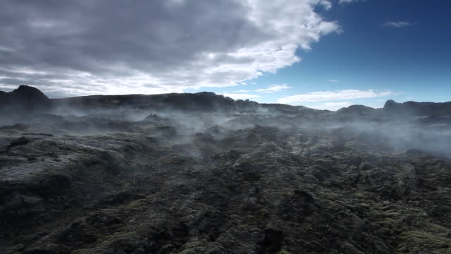 WS View of black volcanic rock, steam coming out of ground and blowing across landscape at leirhnjukur / Krafla, Myvatn region, Iceland