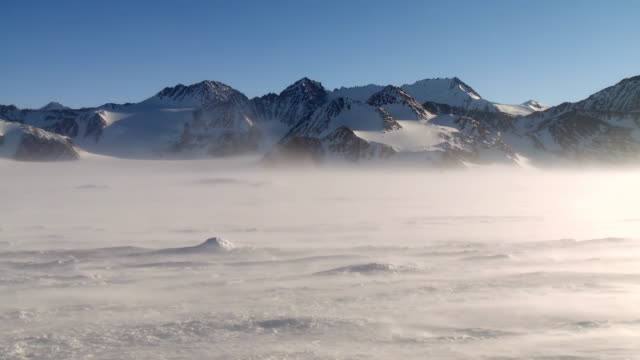 vídeos de stock, filmes e b-roll de ws view of blizzard winds wept landscape of sparkling ice and snow with mountains / union glacier, heritage range, ellsworth mountains, antarctica  - pólo sul