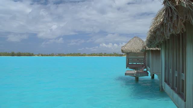 vídeos y material grabado en eventos de stock de ws view of blue lagoon with thatched huts / bora bora, tahiti  - territorios franceses de ultramar
