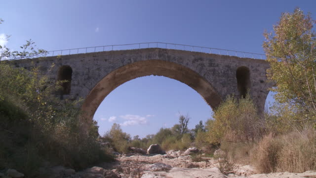 ms view of blue sky behind of old bridge / apt, provence, france  - apt stock videos and b-roll footage