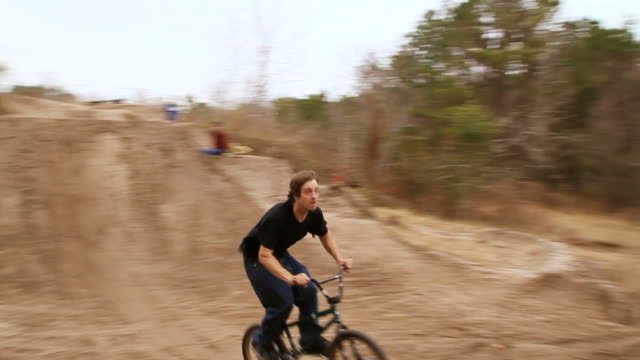 ws pan view of bmx rider jumping over dirt mounds and crashing and falls off bike / jacksonville, florida, usa - bmx stock-videos und b-roll-filmmaterial
