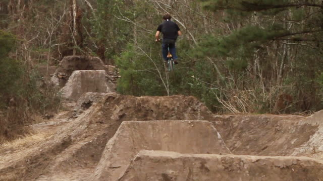 ws view of bmx rider jumping over dirt mounds / jacksonville, florida, usa - un ragazzo adolescente video stock e b–roll