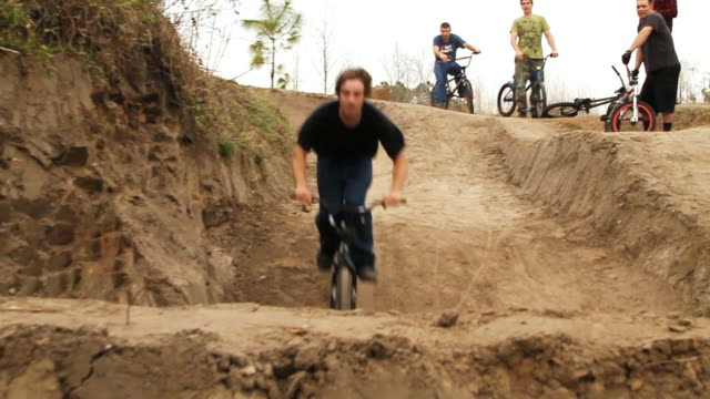 ws pan view of bmx rider jumping over dirt mounds / jacksonville, florida, usa - un ragazzo adolescente video stock e b–roll