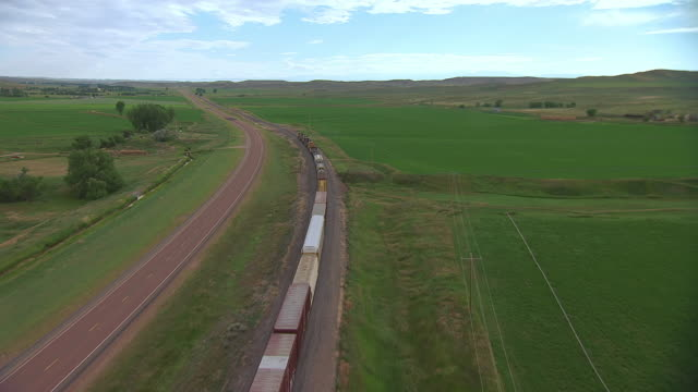 vidéos et rushes de ws aerial ts view of bnsf train going through countryside in sheridan county / wyoming, united states - wyoming