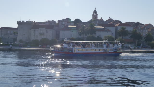 View of boat in Luka Korculanska Bay leaving Korcula Old Town, Korcula, Dalmatia, Croatia, Europe