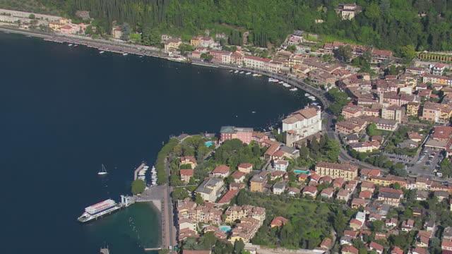 WS AERIAL View of boat marina buildings and trees / Lake Garda, Trentino, Verona, Brescia