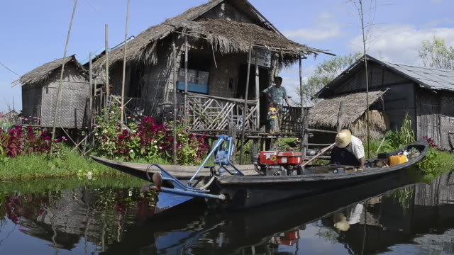ms pov ts view of boat moving along floating village and family in her house / ywama, shan state, myanmar - travel destinations stock videos & royalty-free footage