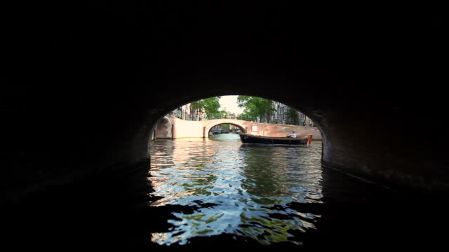 ws pov view of boat moving under arch bridge / amsterdam, the netherlands, holland - arch bridge stock videos and b-roll footage